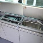 Le Cityvan intègre un évier avec robinet et un réchuad à gaz, rangés dans un meuble de cuisine très étroit