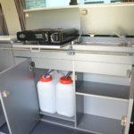 Meuble de cuisine très fin avec un évier, un réchaud à gaz et des réserves d'eau propre et d'eau usée