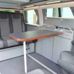 Le Cityvan de chez Reimo, sur la base du Volkswagen T6, prospose une banquette 3 places avec un coin repas complet (table, évier, réchaud à gaz)
